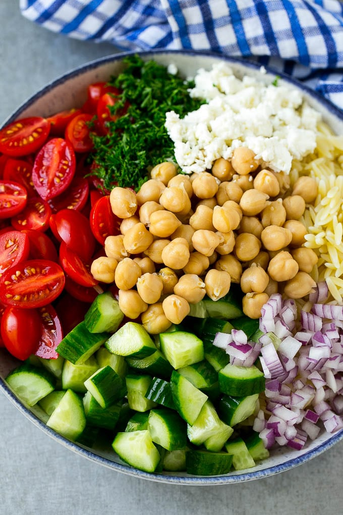 A bowl of orzo pasta, cucumbers, cherry tomatoes, feta cheese, red onions, herbs and chickpeas.