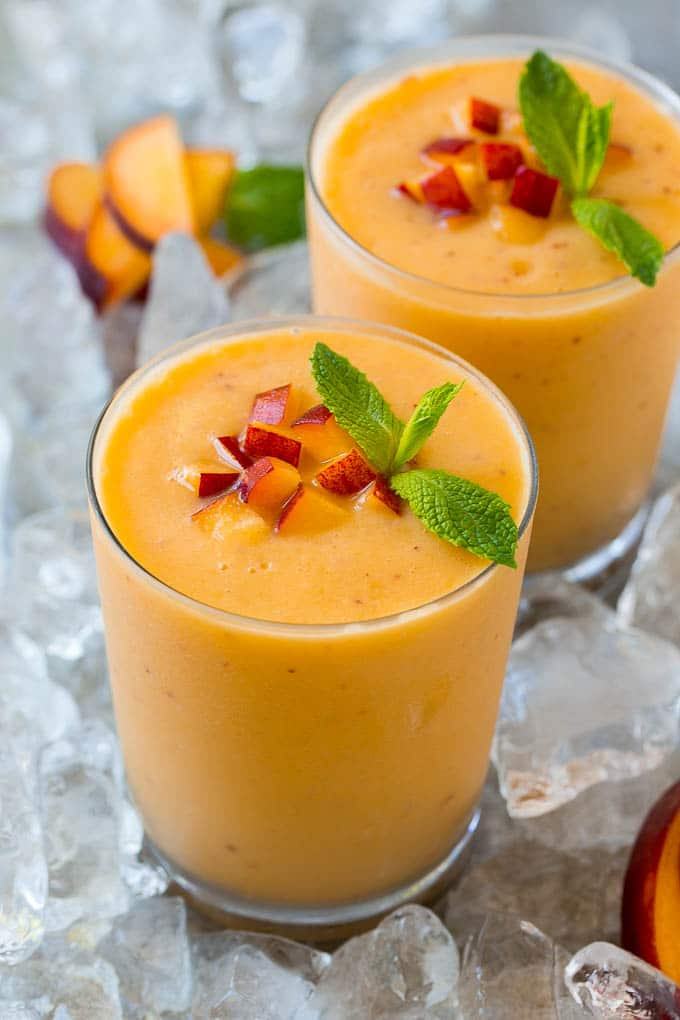 Peach smoothie in a glass topped with fresh peaches and mint.