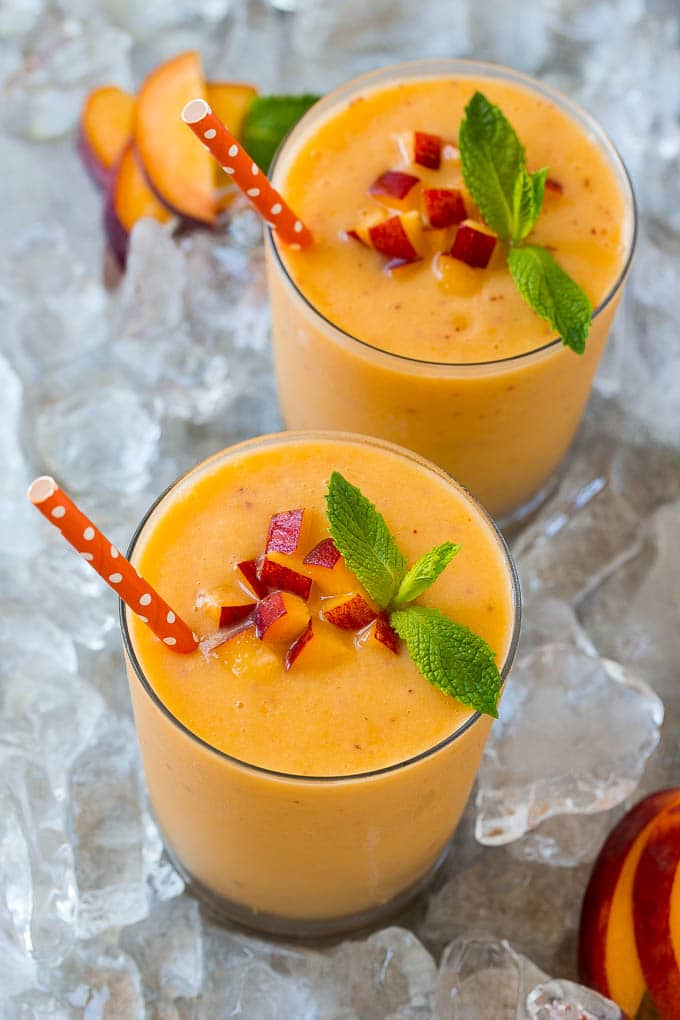Two glasses of peach smoothie on ice, topped with fresh peaches.