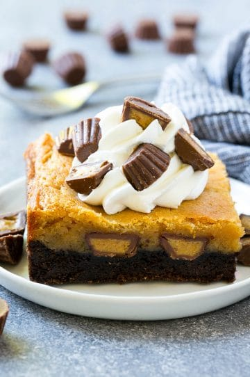 Peanut butter chocolate gooey butter cake topped with whipped cream and chopped peanut butter cups.