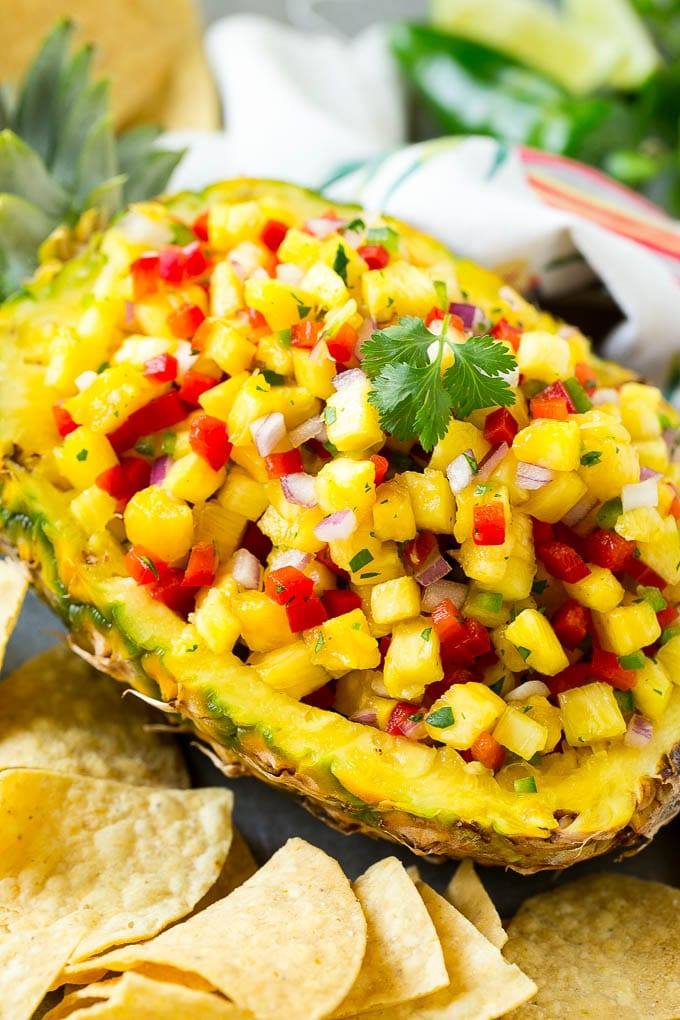 A pineapple boat filled with pineapple salsa.