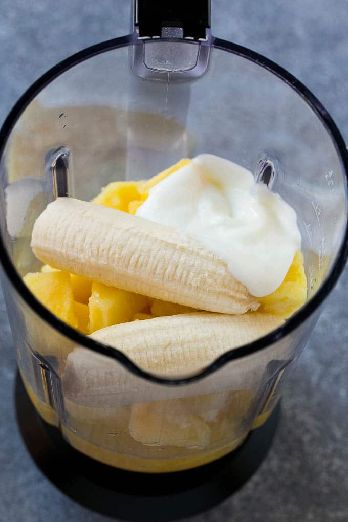 Frozen pineapple, pineapple juice, banana and yogurt in a blender.