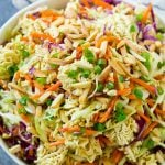 A bowl of ramen noodle salad with cabbage, noodles, green onions and almonds.