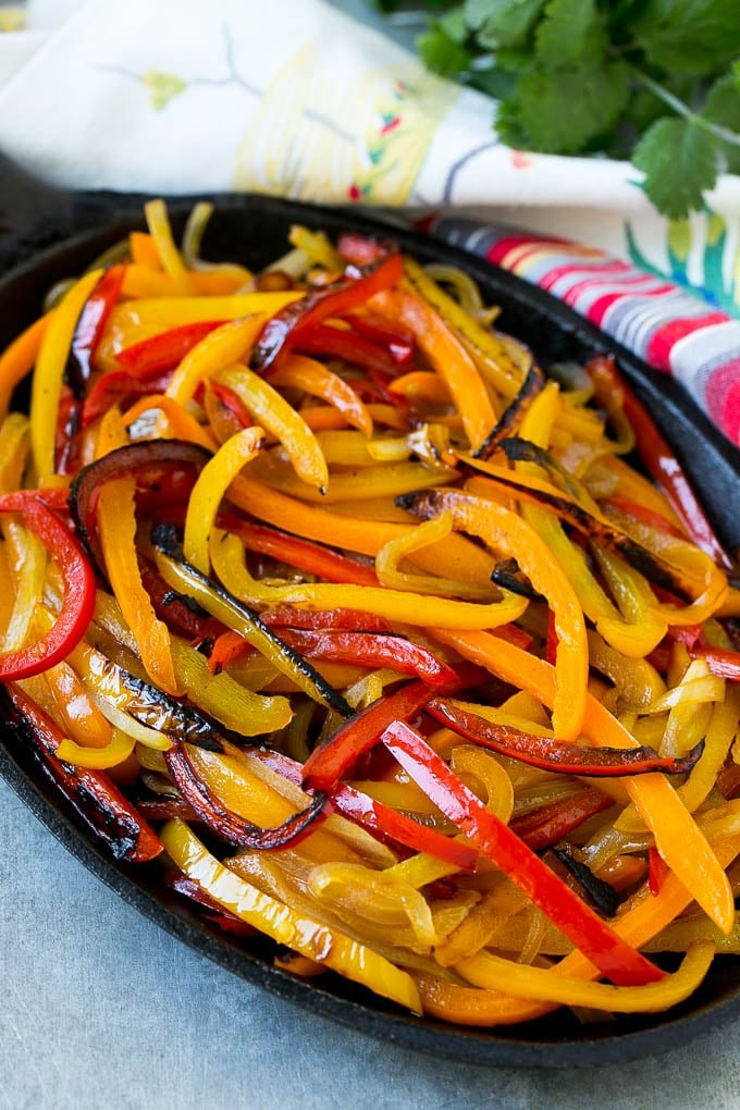 Blackened bell peppers and onions in a pan.