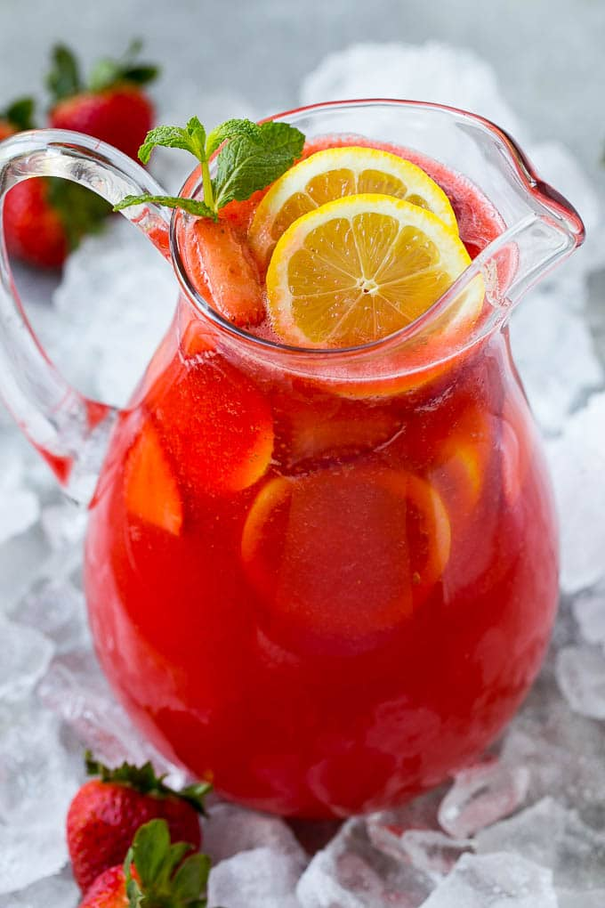 A pitcher of strawberry lemonade garnished with sliced lemons and mint.