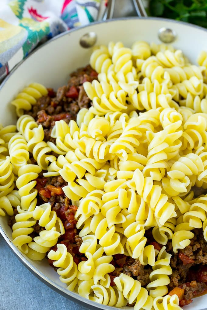A skillet of cooked ground beef seasoned with tomatoes, and rotini pasta.