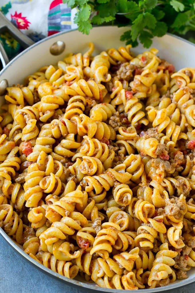 Rotini pasta mixed with ground beef and tomatoes in a creamy sauce.