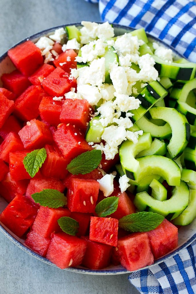 A bowl of cubed watermelon, sliced cucumbers, feta cheese and mint leaves.