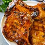 BBQ pork chops are bone in pork chops that have been grilled and topped with barbecue sauce.