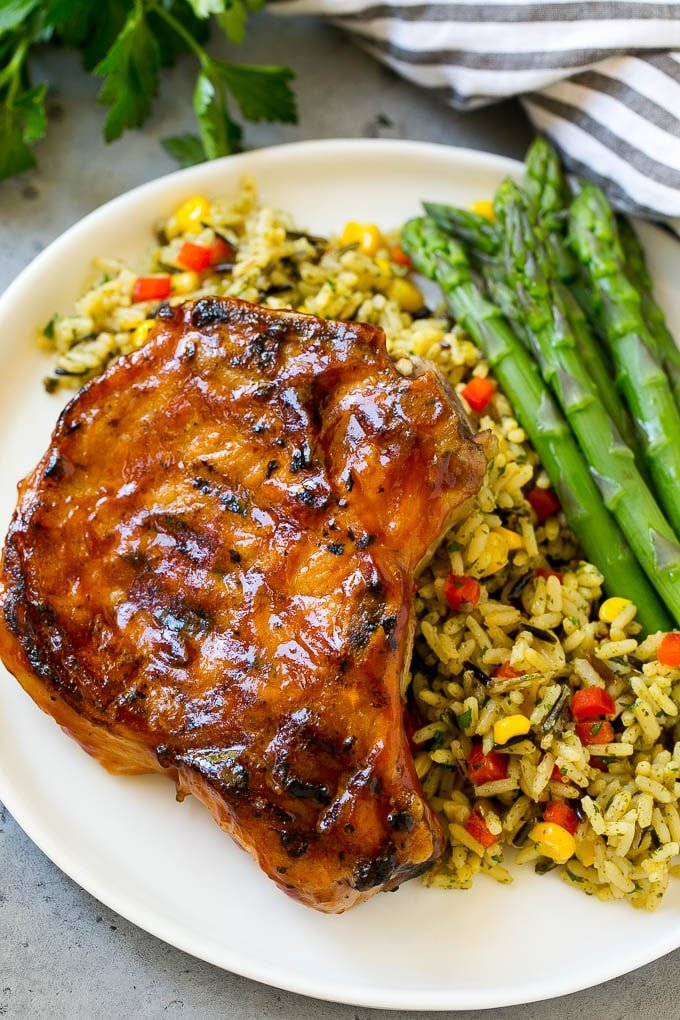 Grilled BBQ pork chops served over rice pilaf with a side of asparagus.