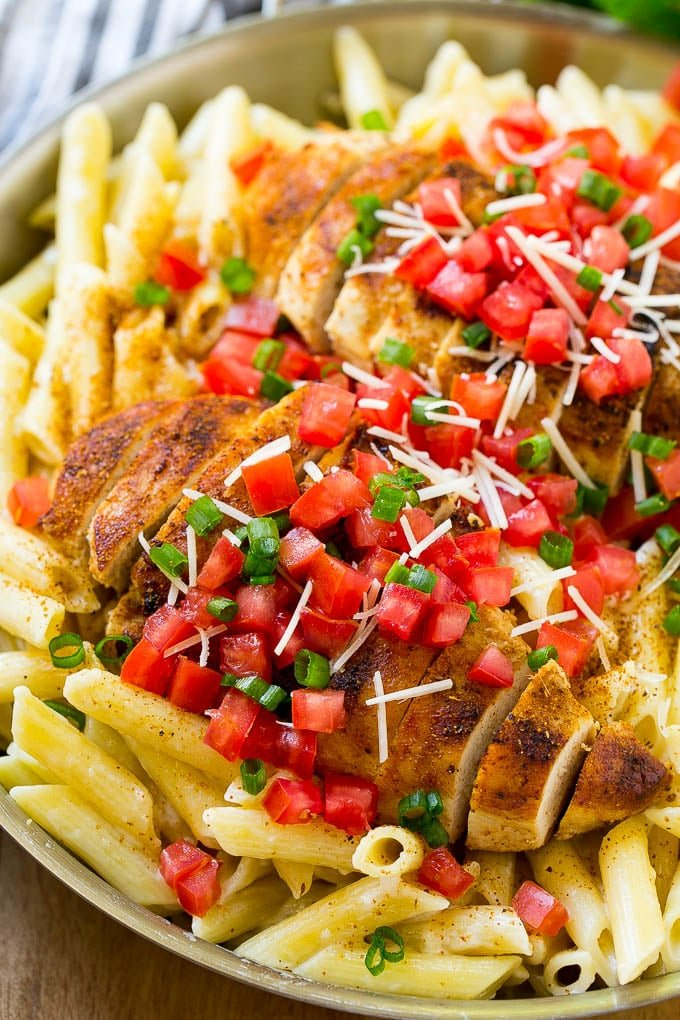 Cajun chicken pasta with grilled chicken breast, creamy penne pasta, tomatoes and green onions.