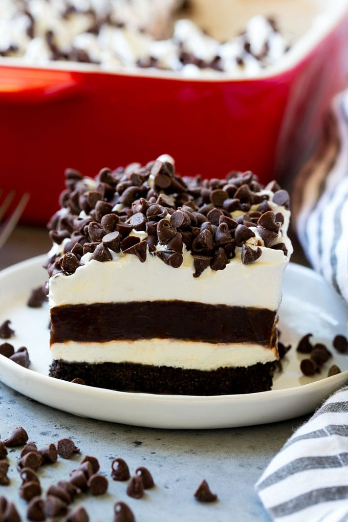 A slice of chocolate lasagna with layers of cookie crust, cheesecake and chocolate pudding.