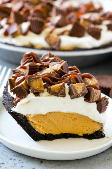 A slice of chocolate peanut butter pie topped with whipped cream, chocolate sauce and peanut butter cups.