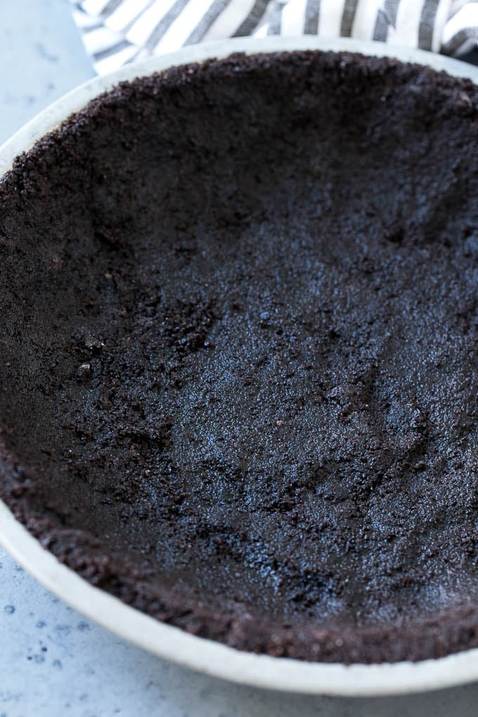 Chocolate cookie crust in a pie tin.