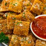 A plate of fried ravioli topped with parmesan and parsley, and served with a side of marinara sauce.