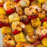 Skewers of jerk shrimp and pineapple, topped with parsley.