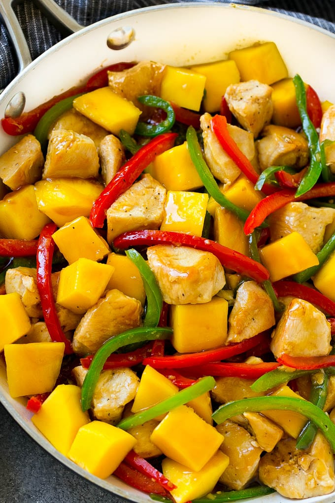 Mango chicken in a pan with red and green peppers.