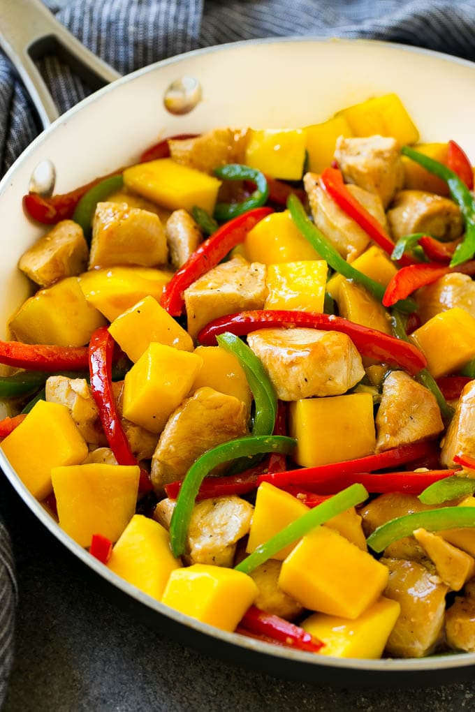 Mango chicken in a skillet with red and green sliced peppers.