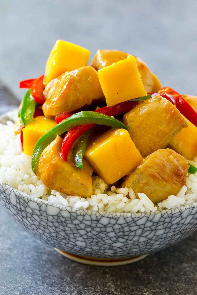 A bowl of mango chicken served over rice.