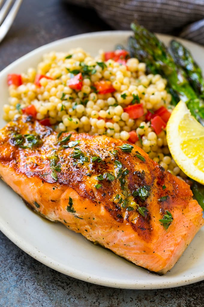 Marinated salmon served over couscous with asparagus on the side.