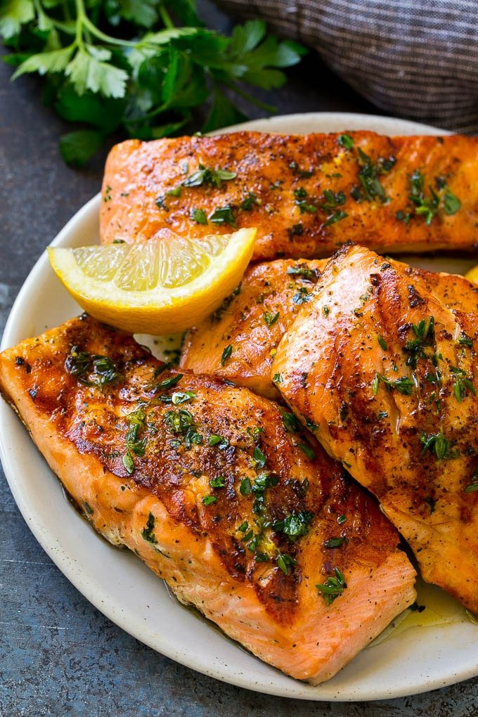 A platter of marinated salmon fillets that are grilled and topped with fresh herbs.
