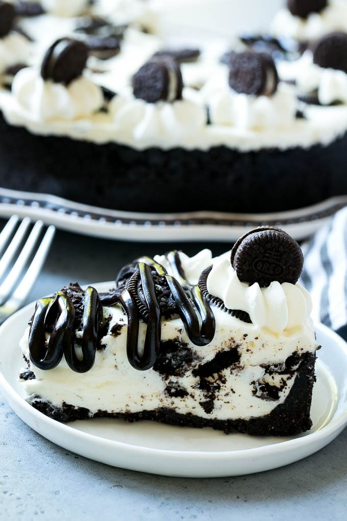 A slice of no bake oreo cheesecake topped with whipped cream and hot fudge sauce.