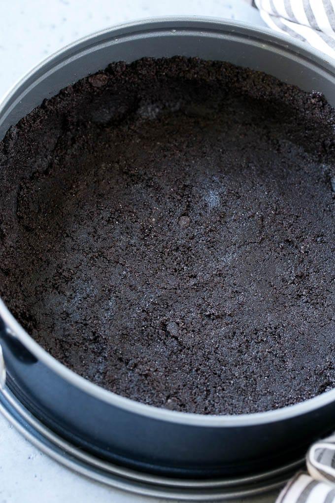 An oreo cookie crust in a springform pan.