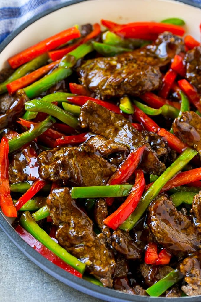 Pepper steak stir fry with thinly sliced steak and red and green bell peppers in a savory sauce.