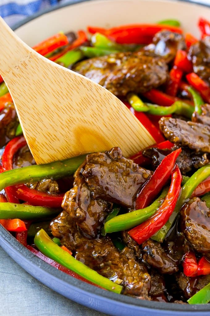 Pepper steak stir fry with a serving utensil in it.