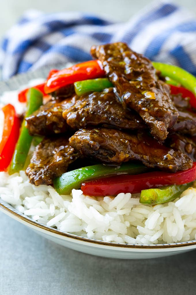 A bowl of rice topped with pepper steak stir fry.