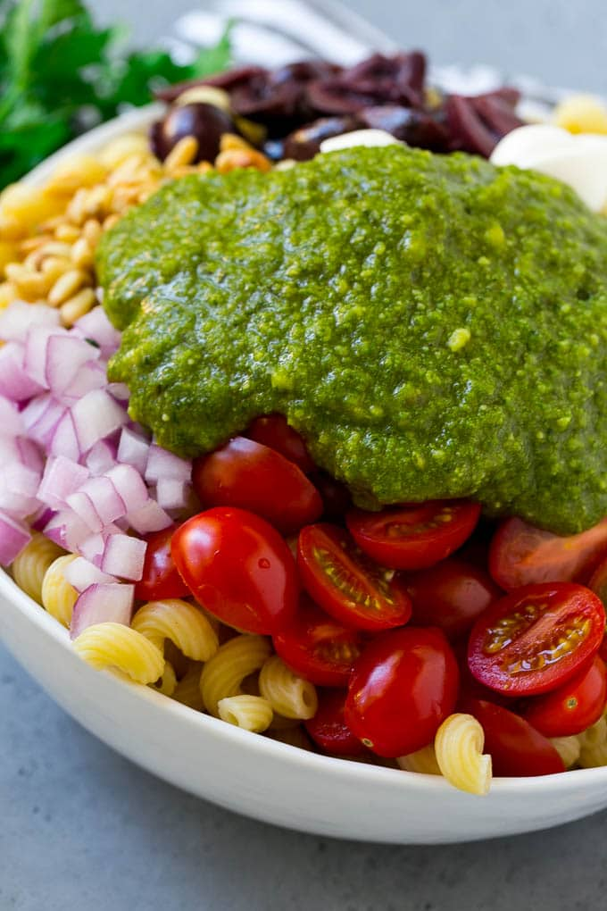 Vegetables and corkscrew pasta topped with fresh pesto.