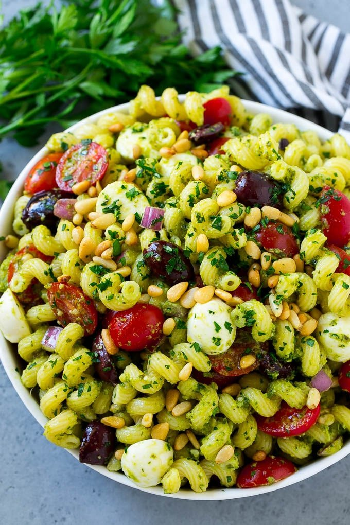 A bowl of pesto pasta salad topped with pine nuts and chopped parsley.
