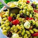 Pesto pasta salad with cherry tomatoes, olives, mozzarella balls, pine nuts and red onion.