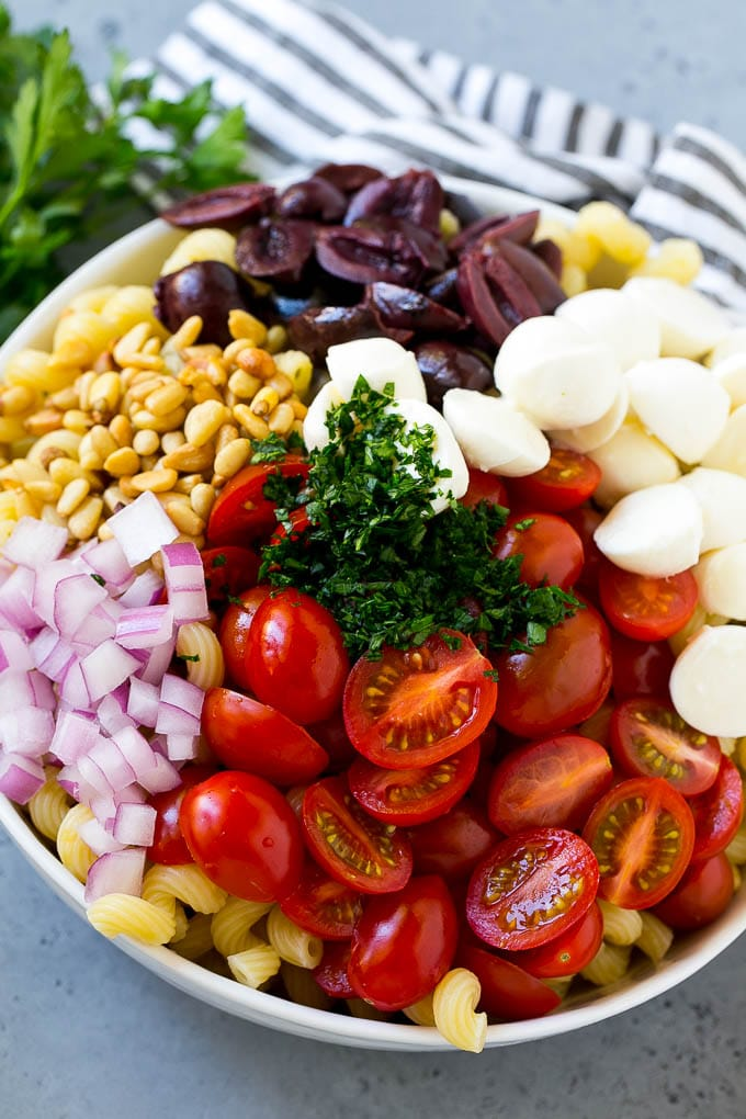 Pasta with cherry tomatoes, mozzarella balls, kalamata olives, parsley and red onion.