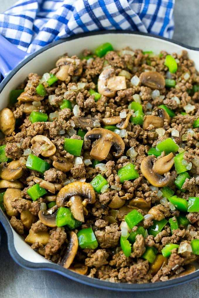 A skillet of browned hamburger meat, mushrooms, onions and bell peppers.