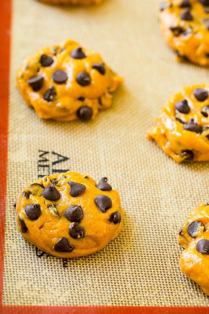 Dollops of pumpkin chocolate chip cookie dough on a baking sheet.