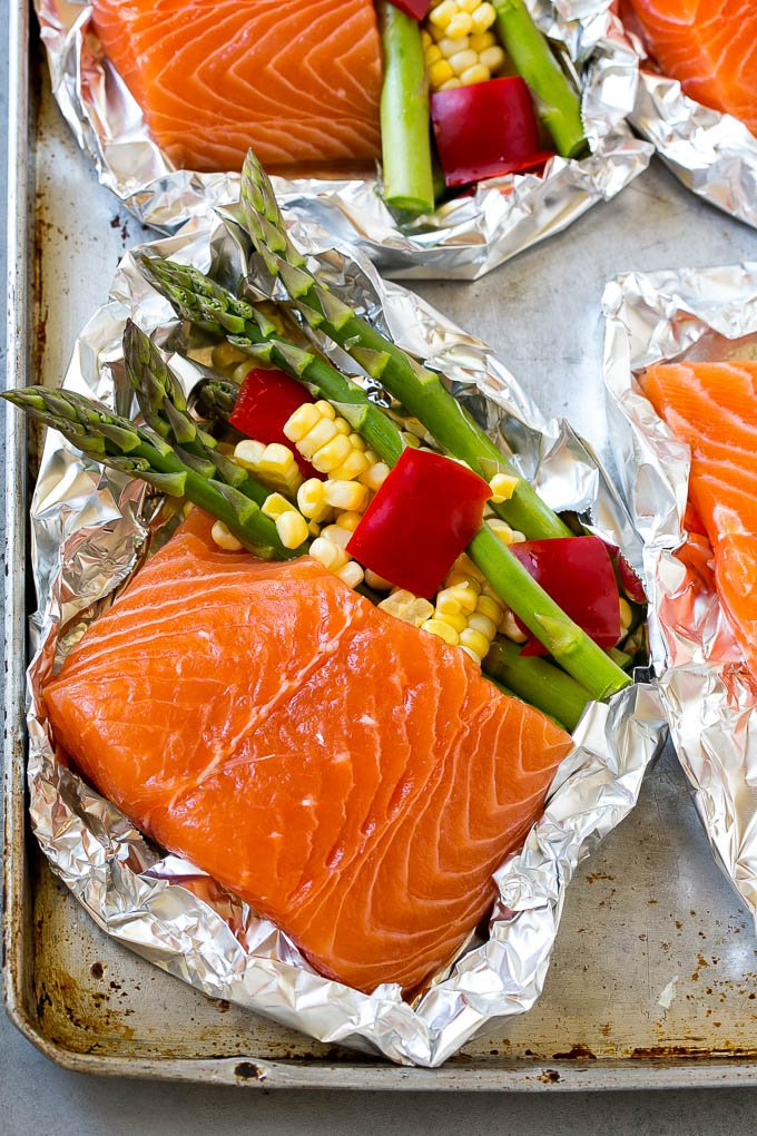 Raw salmon fillets with asparagus in foil.