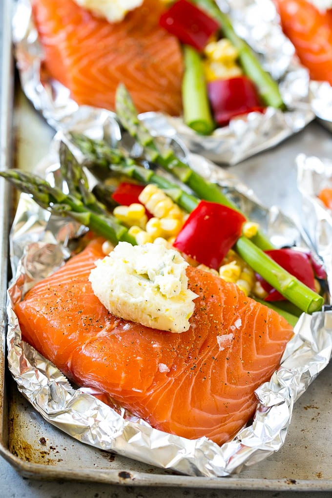 A salmon fillet topped with seasoned butter in a foil packet with vegetables.