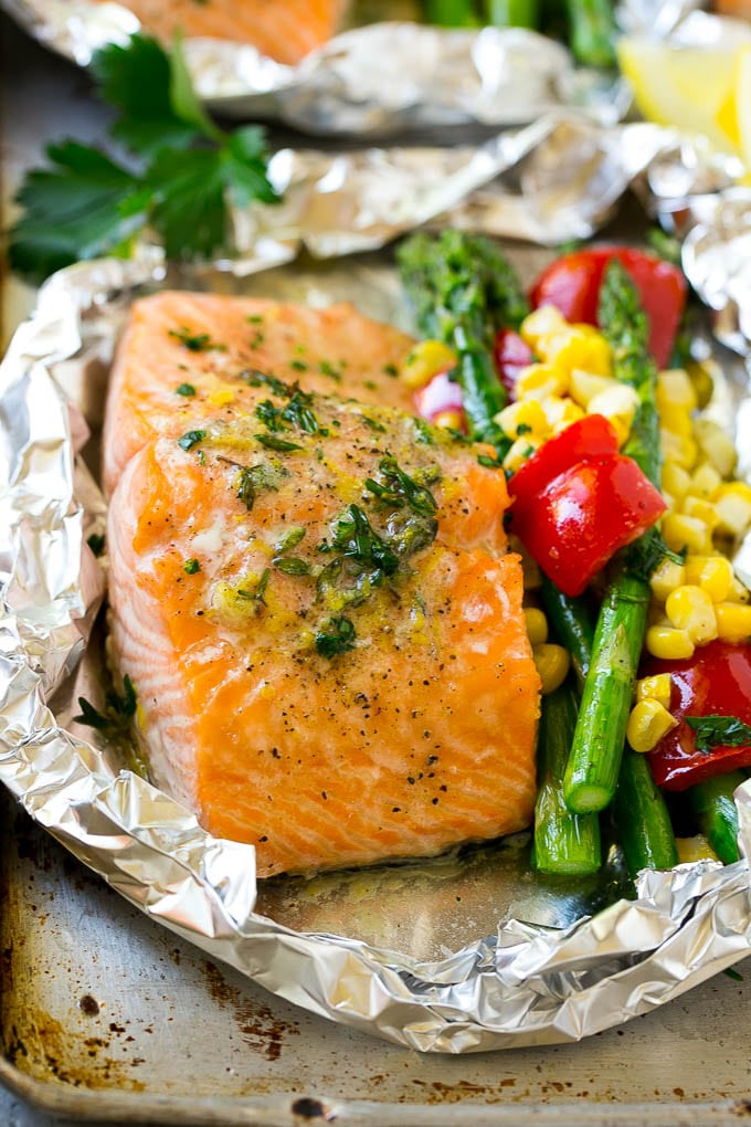A salmon foil packet with asparagus, corn and red bell pepper.