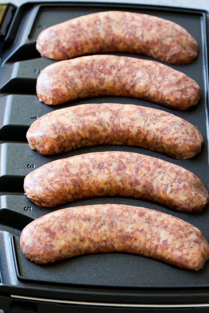 Sausages cooking in a sizzling sausage grill.