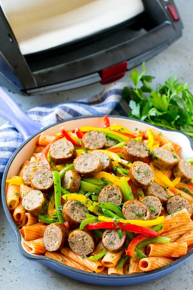 Sausage and pepper pasta in a skillet with a sausage grill in the background.