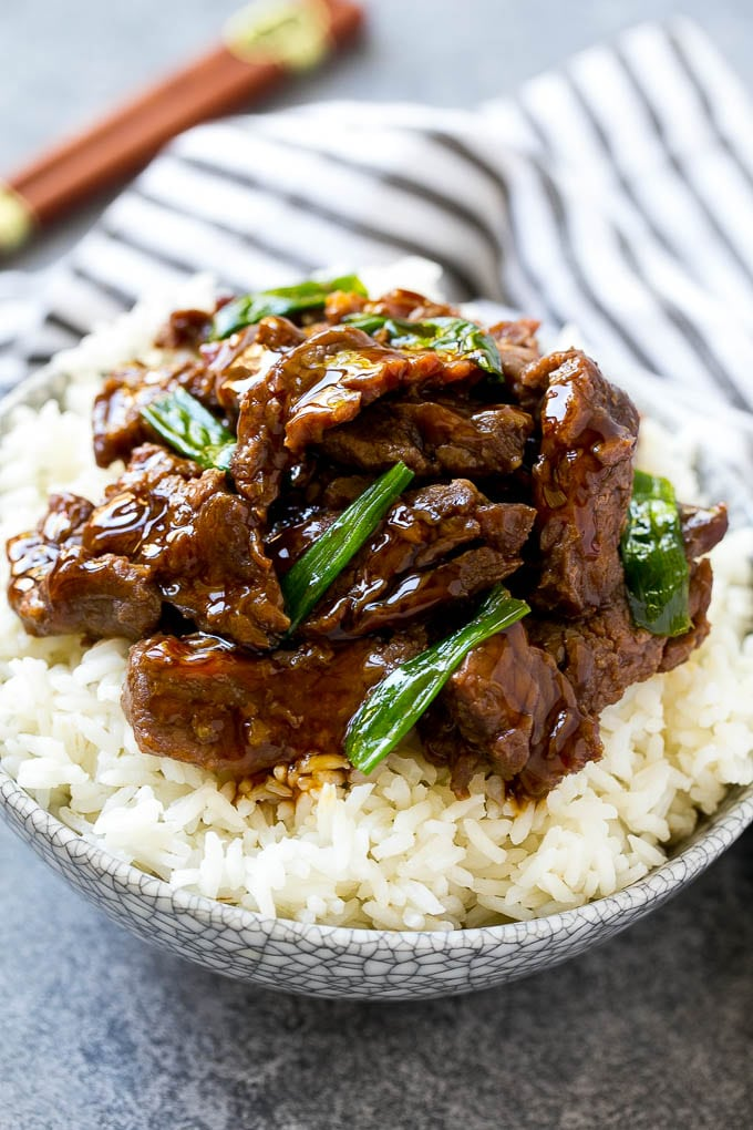 A bowl of rice topped with slow cooker mongolian beef.