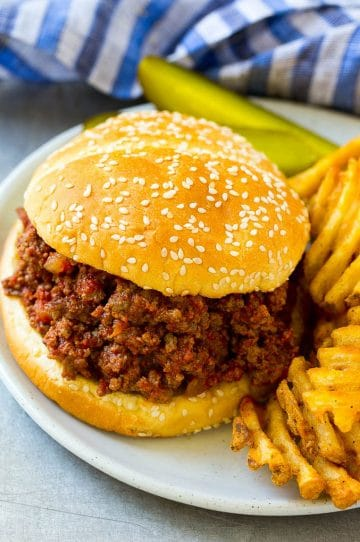 Slow cooker sloppy joe on a bun served with fries and pickles.