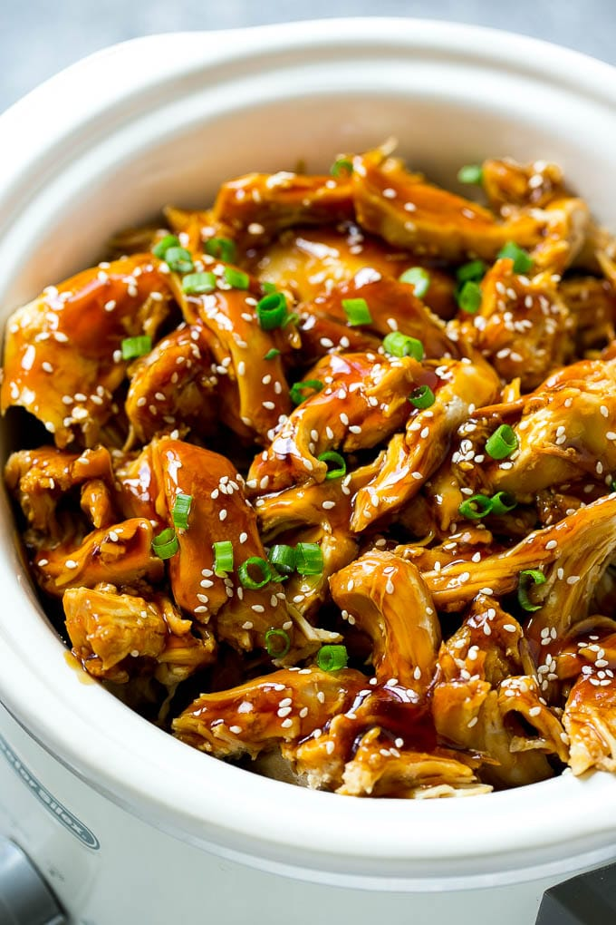 Slow cooker teriyaki chicken with shredded chicken breasts, homemade teriyaki sauce, sesame seeds and green onions.