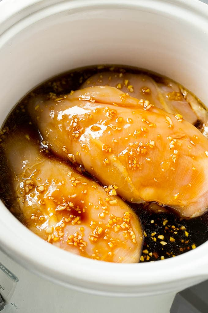 Chicken breasts in a crock pot with soy sauce, garlic and ginger.