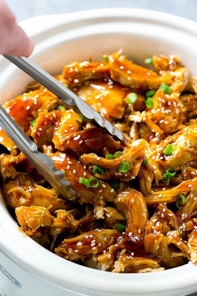 A slow cooker full of teriyaki chicken with tongs in it.