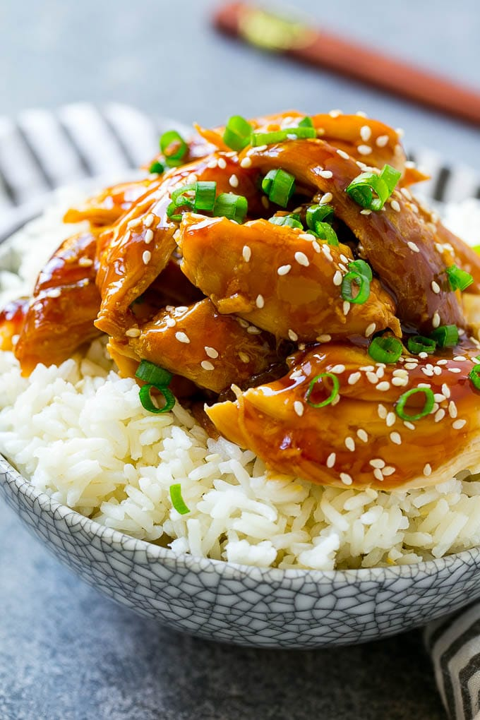 A bowl of rice topped with shredded crock pot teriyaki chicken.