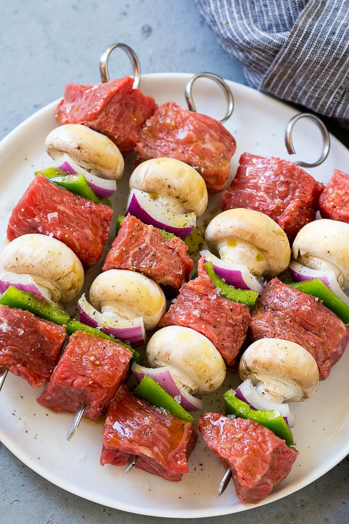 Skewers of beef, mushrooms, peppers and onions on a plate.
