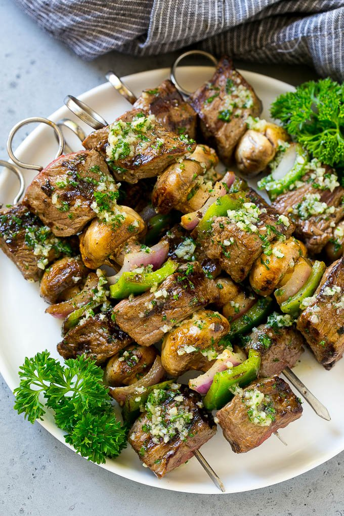 A plate of grilled steak kabobs with garlic butter.