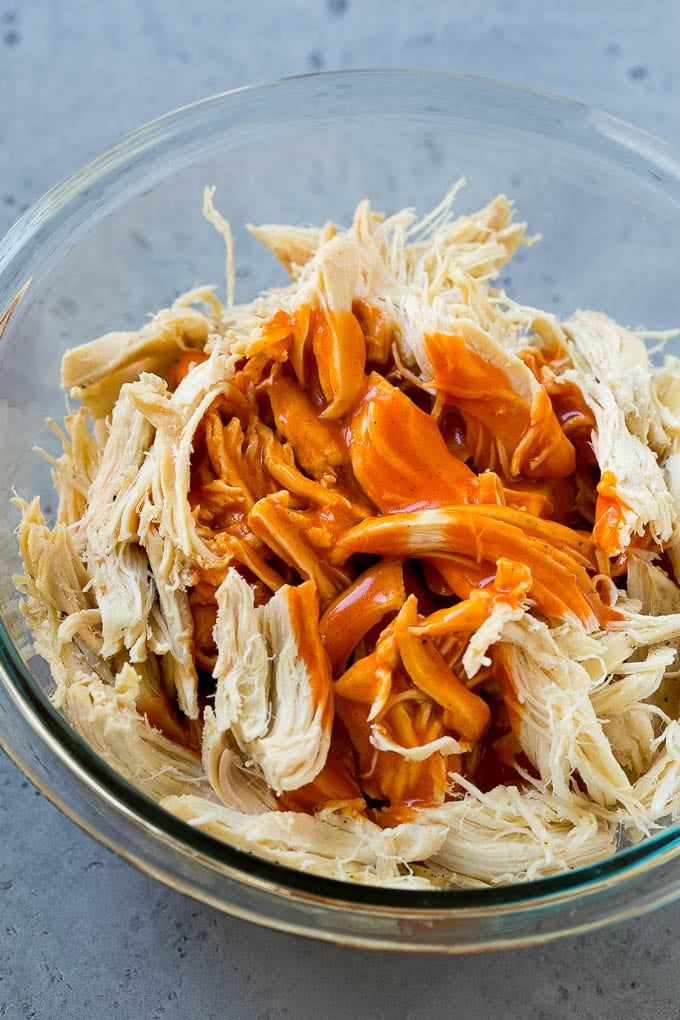 Shredded chicken in a bowl with buffalo sauce.